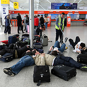 STRANDED PASSENGERS AT STANSTED AIRPORT IN ESSEX ON FRIDAY MORNING AFTER THE AIRPORT REMAINED CLOSED...Flights across the UK are to remain grounded for a second day as volcanic ash from Iceland drifts across Europe...Air traffic control body Nats extended its restrictions on UK airspace until at least 0100BST on Saturday. ..A tiny number of services will be permitted to fly into and out of Northern Ireland, western Scotland and south-west England. ..The continuing volcanic eruption caused cancellations across Europe amid fears the ash could cause engine failures. ..Experts say the tiny particles of rock, glass and sand contained in the ash cloud from the still-erupting volcano could jam aircraft engines, as has happened in previous incidents of planes flying into plumes of volcanic ash. .