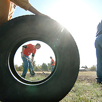 (school gardens on a roll)  --  A rubber tire rolled in to position by Prospect Point Elementary School fourth-grader Max Elston, 10, frames Walla Walla Univeristy volunteers Jon Schaffer (left) and Kayla Quinn working on raking grasses and weeds out of a freshly tilled section of Prospect Point's garden. School garden projects have been on a roll lately, growing into large, year-long undertakings invloving many students and teachers.        Wednesday, October 15, 2008        MZ Photo
