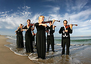 """3-NEWS FEATURE.Paul Kane (Getty Images).Musicians from the West Australian Symphony Orchestra perform a """"Symphony in the Sea"""" at North Cottesloe Beach."""