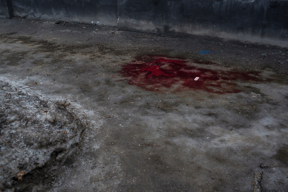 DONETSK, UKRAINE - JANUARY 30, 2015: Blood stains an icy sidewalk after at least two men were killed when a mortar or rocket struck the road and exploded in Donetsk, Ukraine. At least five other people were killed in a separate attack nearby when a rocket struck the parking lot outside a center for the distribution of humanitarian aid. CREDIT: Brendan Hoffman for The New York Times