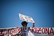 Geronimo Ramirez protests the Supreme Court's rulings on Arizona's immigration law outside the Scottsdale Plaza Resort where Gov. Mitt Romney is holding a fundraiser in Scottsdale, Arizona, June 25, 2012.