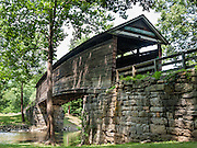 """Humpback Covered Bridge, built in 1857, is the oldest remaining covered bridge in the state of Virginia. Humpback Bridge is one of the few remaining covered bridges in the USA built higher in the middle than on either end (with a humpback 4 feet or 1.2 meters high). The bridge spans 109 feet (33 m) across Dunlap Creek (a tributary of Jackson River), near Covington, Virginia. Covered wooden bridges averaged ten times the lifespan of uncovered ones. Sometimes referred to as """"kissing bridges"""" during the modest era of the late 1800s, covered bridges allowed horse and buggy passengers kissing privacy. Two former non-covered bridges here (built in the 1820s and 1838) were destroyed by floods, and a third bridge collapsed in 1856 due to heavy use and weathering. All three bridges were a part of the James River and Kanawha Turnpike, a heavily traveled mountain road that connected the Shenandoah Valley with the Alleghany Mountains and westwards. The decking, unlike houses and other structures, could not be painted to prevent deterioration, as the traffic from horses and wagons would quickly remove any available paints of the era. The Humpback Covered Bridge was used from 1857 to 1929, when a steel truss bridge was built for US Highway 60 immediately to the north. The bridge was listed in the National Register of Historic Places in 1969. The bridge retains most of its original 1857 hand-hewn white oak and hickory support timbers and decking, but most of the walls and roofing have been replaced several times. The supports incorporate a unique curved multiple kingpost-truss system that is not found in any other surviving wooden bridge in the USA. The bridge is a unique design not duplicated anywhere else. How to reach Humpback Bridge: Take Exit number 10 off of Interstate 64 in Virginia and follow signs, 1 mile east. It is 3 miles west of Covington, Virginia adjacent to U.S. Highway 60 off Rumsey Road (SR 600)."""