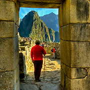 South America, Peru, Andes, Andes Mountains, Machu Picchu. A loone hiker at the main entrance to ancient Machu Picchu, last refuge of the vanished Inca civilization in the Andes Mountains, Peru.