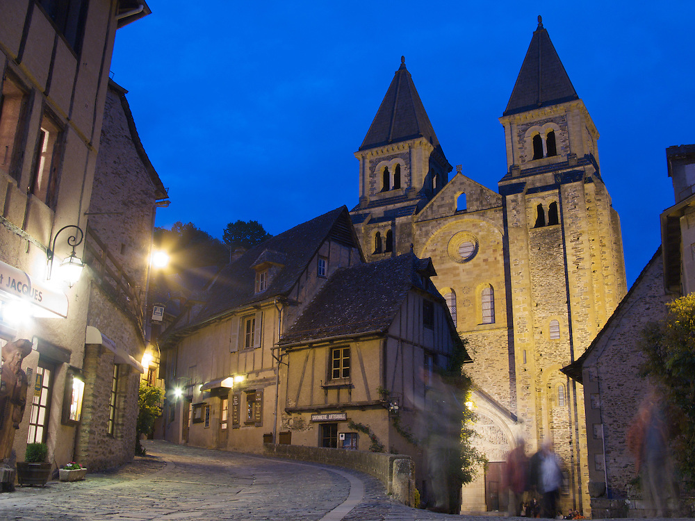 People moved around the front of the Cathedral after returning from restaurants and bars. The old Cathedral is the centrepiece of the World Heritage village of Conques in South-West France.