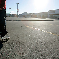 A teen skater hangs in the parking lot of a shopping mall.  Photo by Matthew Healey