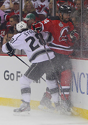 May 30; Newark, NJ, USA; Los Angeles Kings center Jarret Stoll (28) hits New Jersey Devils defenseman Bryce Salvador (24) during the first period of 2012 Stanley Cup Finals Game 1 at the Prudential Center.  The Kings defeated the Devils 2-1.