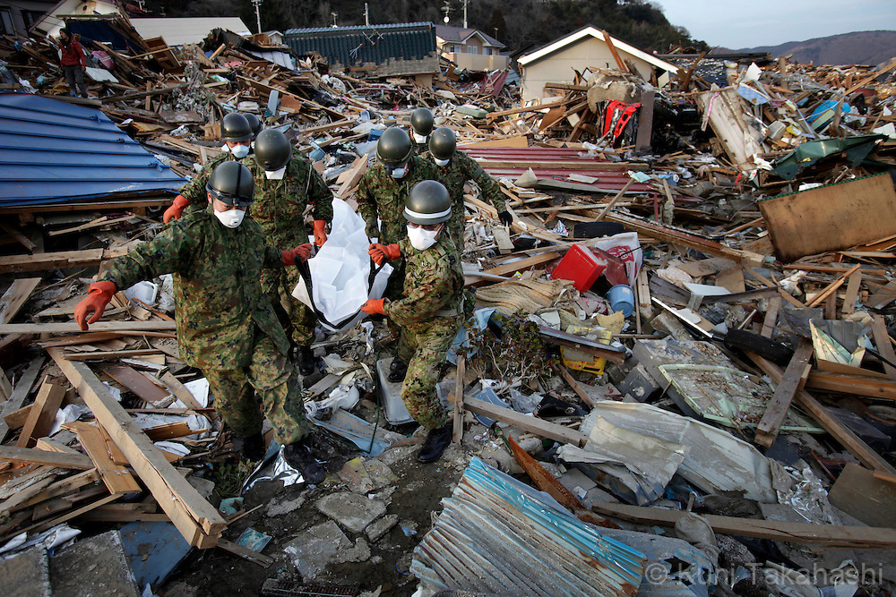 Soldiers of Japanese Self Defense Force carry a body which was recovered under crushed house in Ishinomaki, Miyagi, Japan on April 1, 2011 after massive earthquake and tsunami hit northern Japan. More than 20,000 were killed by the disaster on March 11.<br /> Photo by Kuni Takahashi
