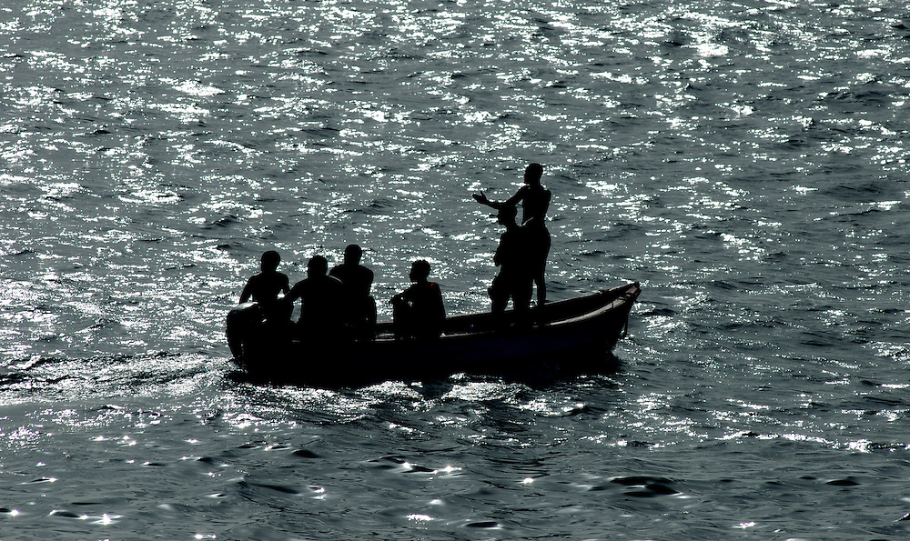 Fishermen in a small boat silhouetted against a low sun, Praia, Santiago, Cape Verde.