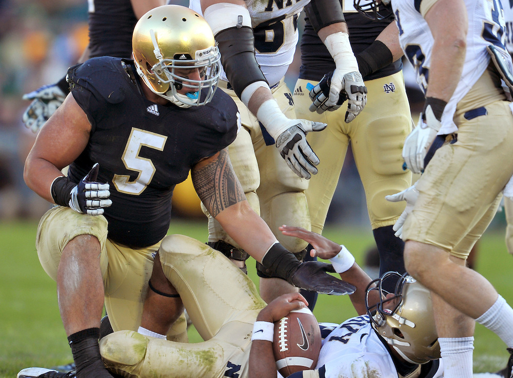 Te'o helps Navy QB Trey Miller up after a sack.