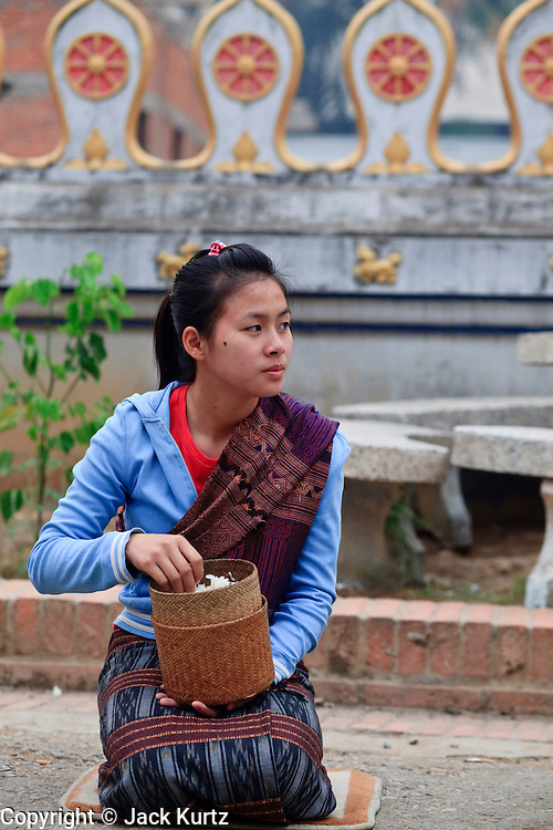 "15 MARCH 2009 -- LUANG PRABANG, LAOS: A woman in Laung Prabang prepares to give alms to Buddhist Monks as they go about their ""Tak Bat,"" Lao for ""monks morning rounds."" The monks collect alms in the form of food from people who line their route. For the monks, it is the only food they get that day, for the people it's a chance to ""make merit."" Luang Prabang is a UNESCO World Heritage Site and the spiritual capital of Laos. There are dozens of ""wats"" or temples and thousands of monks in the city. It is still the center of Buddhist education in Laos. Photo By Jack Kurtz"