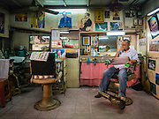 """06 FEBRUARY 2017 - BANGKOK, THAILAND: A barber waits for customers in his shop in what used to be known as Kalabok Market under the Phra Khanong Bridge in the Phra Khanong district of Bangkok. Kalabok is the Thai word for hairdresser and the market was called Kalabok because there were many barbershops and hairdressers under the bridge. In 1985, the city changed the name of the market to """"Singha Market."""" There are still about 10 small men's barbershops, most with just one barber, and four women's salons, most with one hairdresser,  under the bridge.      PHOTO BY JACK KURTZ"""