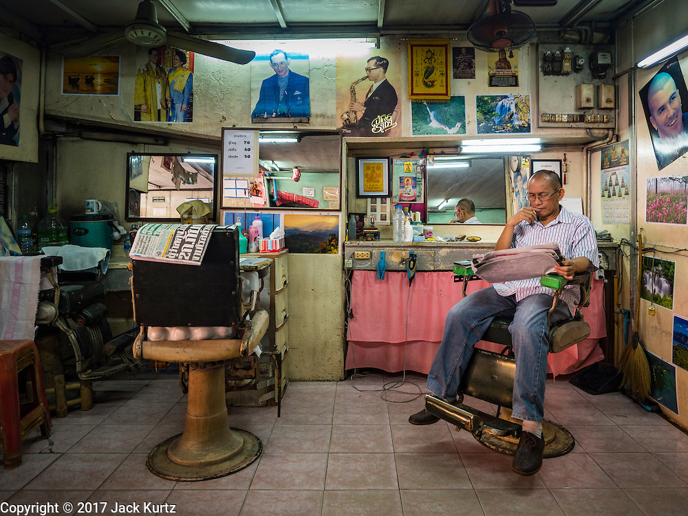 "06 FEBRUARY 2017 - BANGKOK, THAILAND: A barber waits for customers in his shop in what used to be known as Kalabok Market under the Phra Khanong Bridge in the Phra Khanong district of Bangkok. Kalabok is the Thai word for hairdresser and the market was called Kalabok because there were many barbershops and hairdressers under the bridge. In 1985, the city changed the name of the market to ""Singha Market."" There are still about 10 small men's barbershops, most with just one barber, and four women's salons, most with one hairdresser,  under the bridge.      PHOTO BY JACK KURTZ"