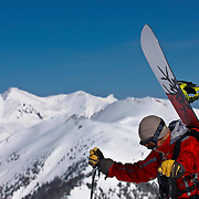 SHOT 3/12/10 11:13:07 AM - A guide pauses while hiking the ridgeline at Silverton Mountain in Silverton, Co. as the San Juan Mountainrange looms in the background. The San Juan Mountains are a rugged mountain range in the Rocky Mountains in southwestern Colorado. Skiing and snowboarding at Silverton Mountain in Silverton, Co. Silverton Mountain is unique amongst ski resorts requiring a guide (most of the season), avalanche gear and limiting the number of daily visitors. There are multiple bowls, chutes, cliffs and natural terrain features to be discovered during a visit to Silverton Mountain. It is the highest Ski Area in North America with a peak of 13,487' and it is also the steepest with no easy way down. The mountain is left in it's natural state with the exception of the avalanche reduction work which occurs. There is only one chair at the mountain though most skiiers and snowboarders will end up hiking in various directions at the top. The mountain also features heliskiing trips for $159 a trip (at the time of visit). The mountain opened in 2002. (Photo by Marc Piscotty / © 2010)
