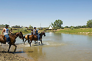 Young Crow Indians cross Little Bighorn River on horses,  Crow Indian Reservation, Montana