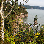Flowerpot Rock and coast at Fownes Head lookout, Fundy Trail Parkway, in Saint John County, Bay of Fundy, St. Martins, New Brunswick, Canada. In St. Martins, drive through the covered bridge on Big Salmon River Road and go 7 km to reach the start of the Fundy Trail Parkway, a 16 kilometer auto route along the Fundy coast ending at Big Salmon River, a former lumbering center. Bay of Fundy has the highest tidal range in the world, due to a resonance of being just the right length (270 km) matching the gravitational pushing cycle of the Moon that causes the tides. Coincidentally, the time it takes a large wave to go from the mouth of the bay to the inner shore and back is practically the same as the time from one high tide to the next. (You can see the effect of resonance for yourself by steadily pushing a long pan of water back and forth: an optimal pushing frequency for a given pan length will build up a high wave of water which sloshes out; but pushing too fast or too slow won't build up the big wave.) Two high tides occur per day, one when the ocean side is nearest the Moon, and one on the side of the Earth most distant from the Moon, about 12 hours and 25 minutes from one high tide to the next. The Bay of Fundy is on the Atlantic coast of North America, on the northeast end of the Gulf of Maine between the Canadian provinces of New Brunswick and Nova Scotia.