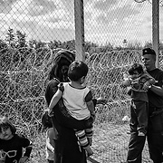 A hungarian police woman brings back the son of a family of refugees after they crossed the hungarian border illegaly from Serbia, on september 12, 2015. Thousands of refugees, most of them from Syria, cross this border everyday with the hope to reach european countries like Sweden or Germany. The next step for them will be to register in Hungary before continuing their long journey.