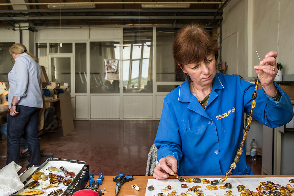 Ruslana Fedchuk, who has worked for 17 years at the government-operated Ukraine Amber factory, makes an amber necklace on Monday, May 30, 2016 in Rivne, Ukraine.
