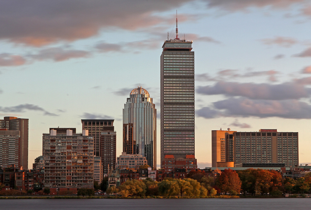 Boston skyline photography showing the Sheraton Hotel, Prudential Center, 111 Huntington Avenue office building and brownstones along the Charles River sun kissed by the late afternoon light shortly before sunset in October.<br />