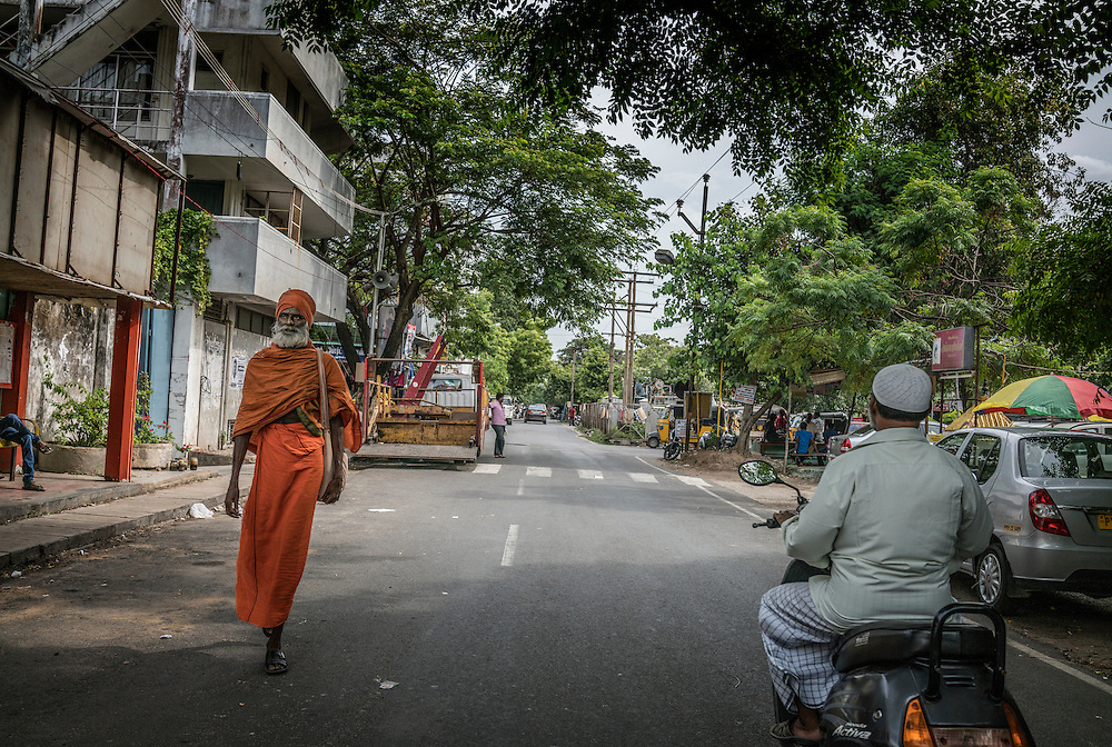 Hindu pilgrim passes a Muslim man on a scooter in one of the most multicultural, multi-religious countries on the planet.  Pondicherry, India.