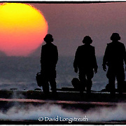 """In this """"Signature Series"""" image by David Longstreath, US sailors on the flight deck of the carrier USS Theodore Roosevelt welcome the dawn during flight operations in the Arabian Sea against the Taliban in Afgahistan."""