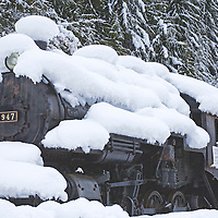 A steam locomotive rests under a heavy blanket of new snow.