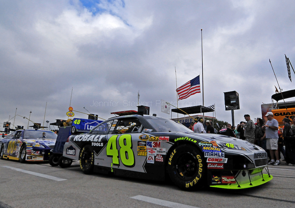 Nov. 8, 2009; Fort Worth, TX, USA; The car of NASCAR Sprint Cup Series driver Jimmie Johnson prior to the Dickies 500 at the Texas Motor Speedway. The American Flag flies at half-mast due to an incident involving Major Nidal Malik Hasan, an army psychiatrist, who killed 13 people and wounded 30 in a shooting at the military base at Fort Hood. Mandatory Credit: Jennifer Stewart-US PRESSWIRE