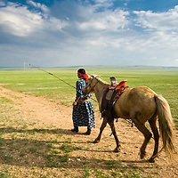 A Mongolian horsemen dressed in traditional clothing and carrying his Uurga (herding pole)   guides his horse out for herding on the grasslands of Inner Mongolia.