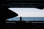 A moment of reflection while looking out one of the aircraft elevators portals on the hanger deck<br /> <br /> Aboard the USS Harry S. Truman operating in the Persian Gulf. February 25, 2016.<br /> <br /> Matt Lutton / Boreal Collective for Mashable