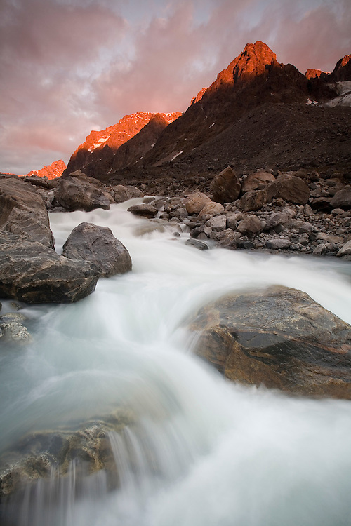 Greenland, Itilleq, Setting midnight sun lights mountain peaks above mountain stream along Itilleq Fjord