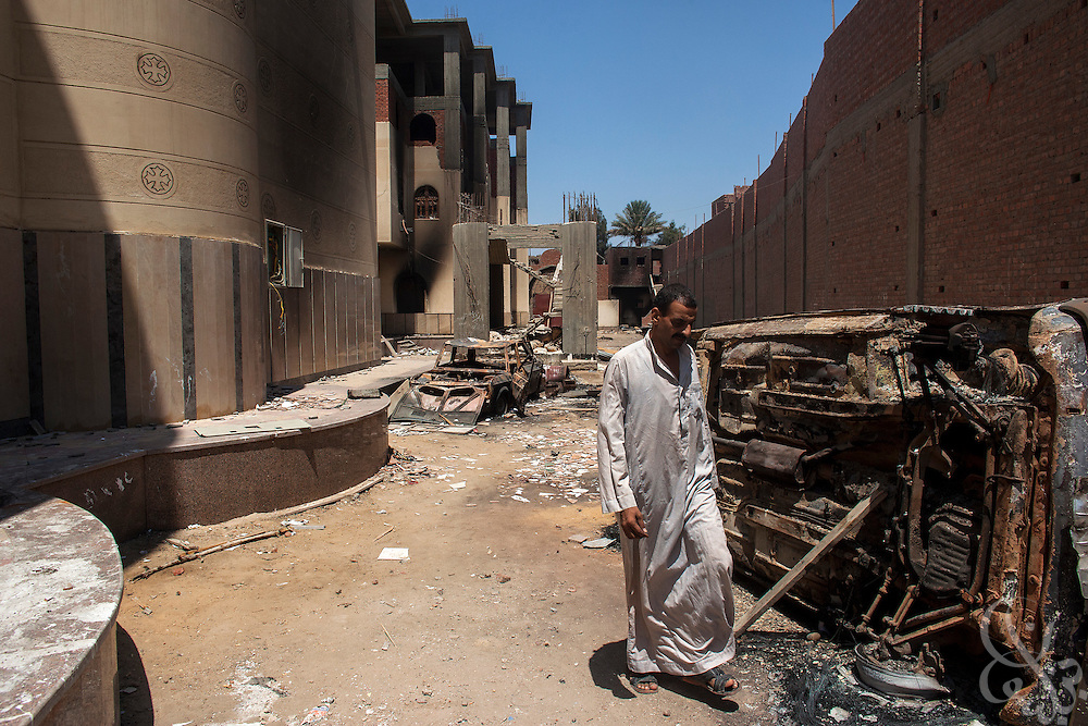 A Coptic Christian Egyptian man walks past destroyed car frames on the grounds of the burned and looted Virgin Mary Church August 20, 2013 after a recent attack by Muslims in the village of Nazla, near el Fayoum, around a 100 kilometers South of Cairo, Egypt.  Coptic Christian villagers report 2 churches and a monastery in the area came under attack by their Muslim neighbors on the same day as Egyptian security forces were moving to forcibly disperse the sit-in camp of the supporters of deposed president Mohamed Morsi.