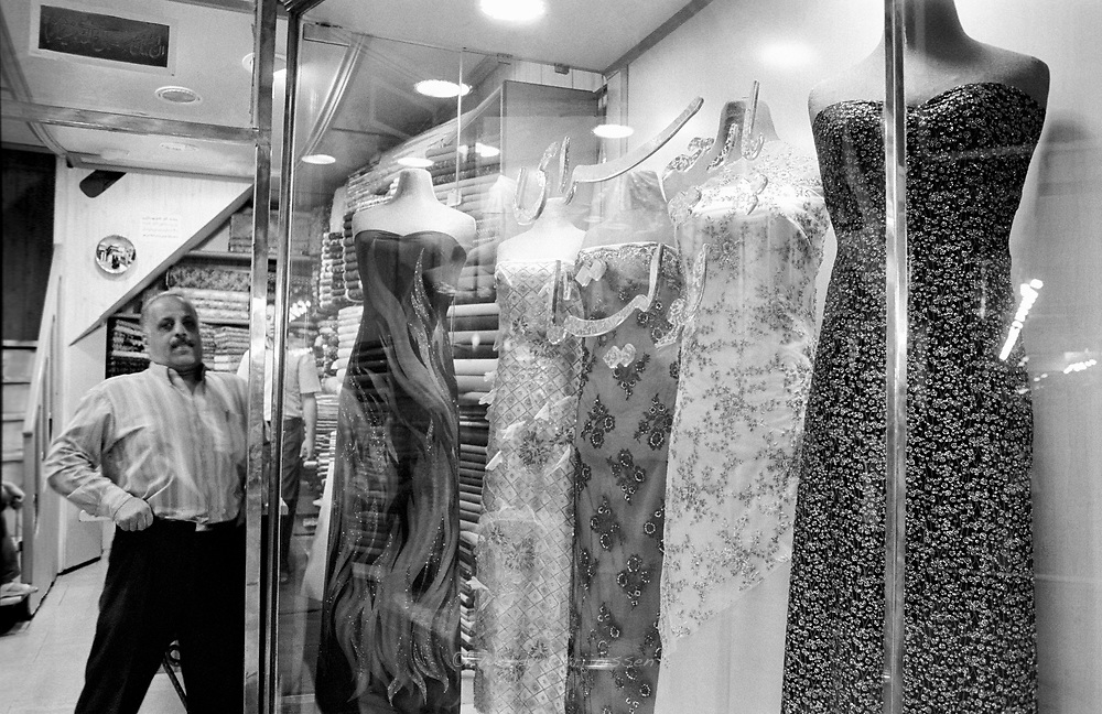 An Iranian shopowner standing in front of his shop, selling partydresses. Tehran, Iran, 2007