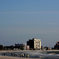 ST. PETE BEACH, FL -- February 13, 2010 -- Vacationers walk along the wide beaches outside of the Postcard Inn in St. Pete Beach, Fla., on Saturday, February 13, 2010.  The beachfront U-shaped hotel, originally built in 1957, was renovated into a throwback surf shack of sorts with rooms featuring surfing imagery and vintage furniture. (Chip Litherland for The New York Times)