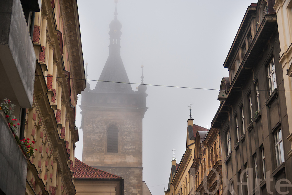 Eerie view of the top of the New Town Hall tower through morning mist as seen from Reznicka street in Prague, Czech Republic
