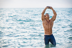 shirtless muscular man wringing out his shirt above his head while standing in the ocean