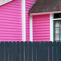 Pink and white house with gray picket fence