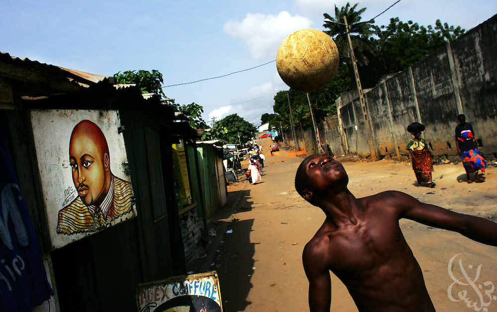 An Ivorian teen heads a ball to pass the time in the Adjame neighborhood of Abidjan, Côte d'Ivoire February 17,2006. Football is an integral part of the social fabric that makes up Ivorian society.