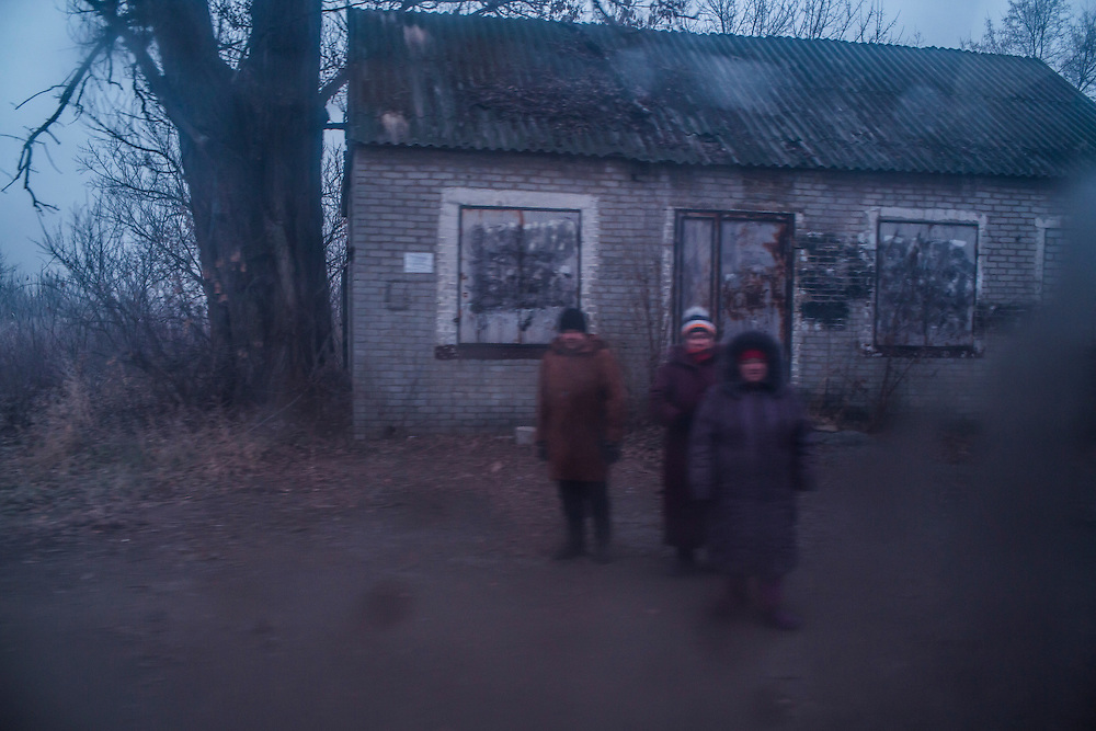 Local residents wait outside along the road for aid from the ICRC to arrive on Friday, December 11, 2015 in Troitske, Ukraine.