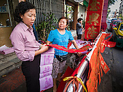 """18 JANUARY 2017 - BANGKOK, THAILAND: A woman shops for hand drawn Chinese New Year calligraphy in Bangkok's Chinatown district, before the celebration of the Lunar New Year. Chinese New Year, also called Lunar New Year or Tet (in Vietnamese communities) starts Saturday, 28 January. The coming year will be the """"Year of the Rooster."""" Thailand has the largest overseas Chinese population in the world; about 14 percent of Thais are of Chinese ancestry and some Chinese holidays, especially Chinese New Year, are widely celebrated in Thailand.      PHOTO BY JACK KURTZ"""