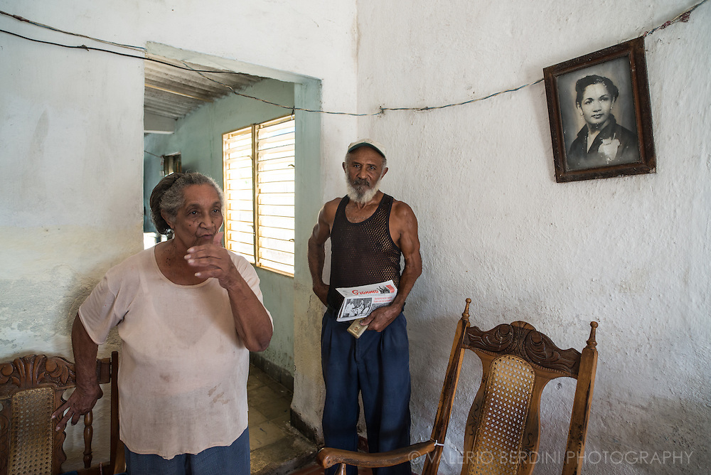 Luiz Antonio Bello Diez old member of Cuban revolutionary Army (ejercito rebelde), who fought key battles in the late 50s in support of the socialist revolution. He stands holding a copy of Granma, the only government newspaper (the only newspaper in Cuba) and his army ID card. Next to him his wife, on the wall a photo of a dead relative. Caibarien. Cuba, 2015.