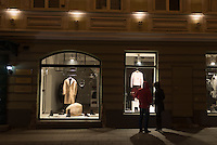 A couple engages in some window shopping at night in Vilnius, Lithuania