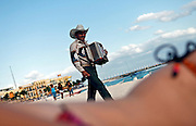 """SHOT 12/2/10 3:30:56 PM - A local musician works the beach looking for tips in Playa del Carmen, Mexico taking in the sights. Playa del Carmen (Xaman Ha' or Pláaya in Modern Maya) is a balneario resort city just south of Cancun on the coast of the Caribbean Sea, in the northeast of the Mexican state of Quintana Roo. The city is the seat of the Solidaridad municipality. In the 2005 census, the city had a population of about 100,383 people and it is rapidly growing in population. It is the third largest city in Quintana Roo, after Cancún and Chetumal. Today Playa del Carmen, or just """"Playa"""" as it is colloquially referred to, is the center of the Riviera Maya concept, which runs from south of Cancún to Tulum and the Sian Ka'an biosphere reserve and has become a major resort and beach destination in Mexico. (Photo by Marc Piscotty / © 2010)"""