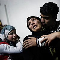 SYRIA - Homs province: One mother and her sons cry the lost of her other two sons, killed by a mortar attack launched by Al Asad forces, in Homs province on February 20, 2012. ALESSIO ROMENZI