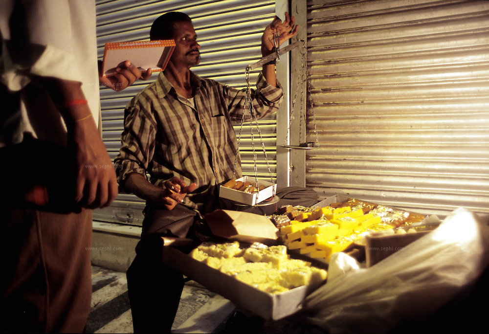 After closing time of the shops, a sweet vendor is selling gulab jamun, barfi, and other delicacies from a make shift stall on the sidewalk in the alleys behind the Jama Masjid in Old Delhi.