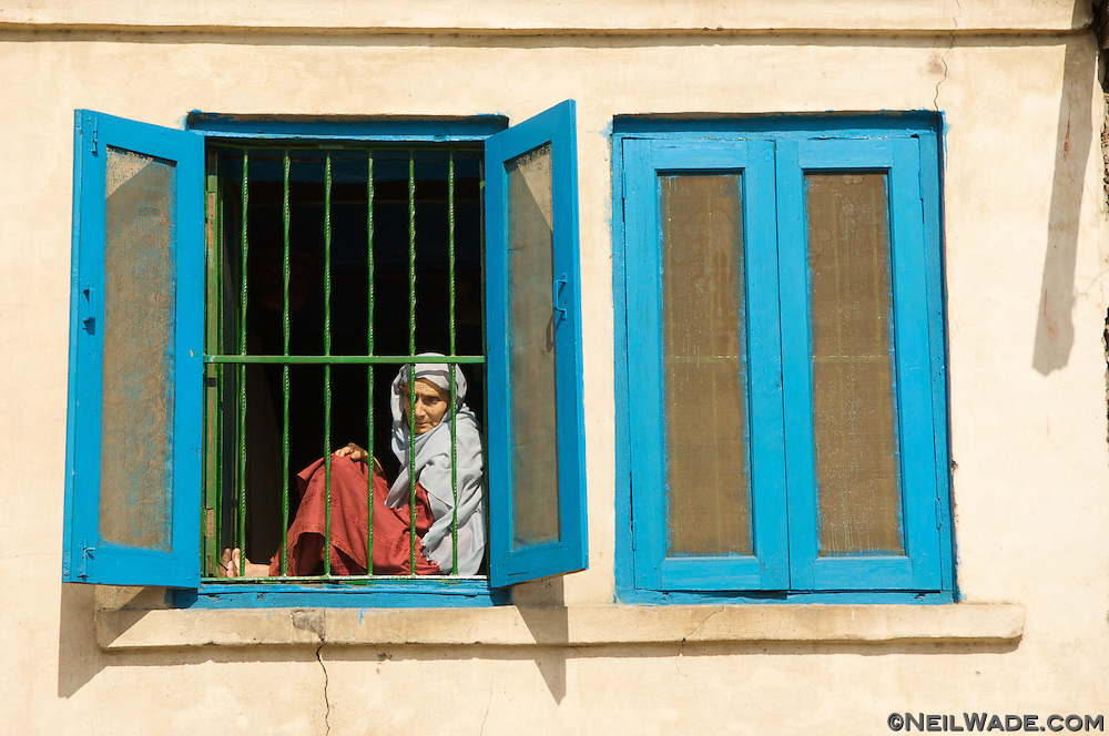 A woman sits in a window watching the traffic in constantly troubled Srinagar, India.