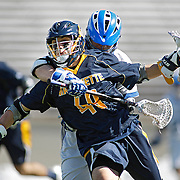 SHOT 3/2/13 1:03:51 PM - Marquette's Connor Bernal #49 tries to muscle his way past Air Force's Bryan Price #13 during their college lacrosse game at Falcon Stadium in Colorado Springs, Co. Marquette won the game 8-6 marking their first ever win as a new program. (Photo by Marc Piscotty / © 2013)