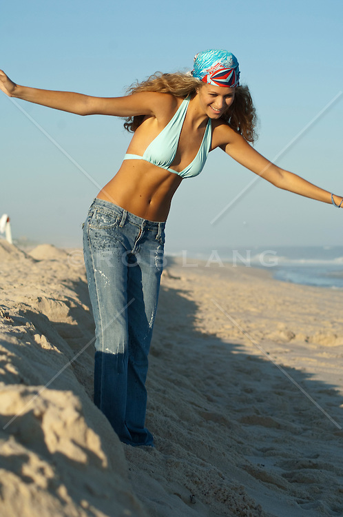 Young girl balancing on a sand mound at the beach