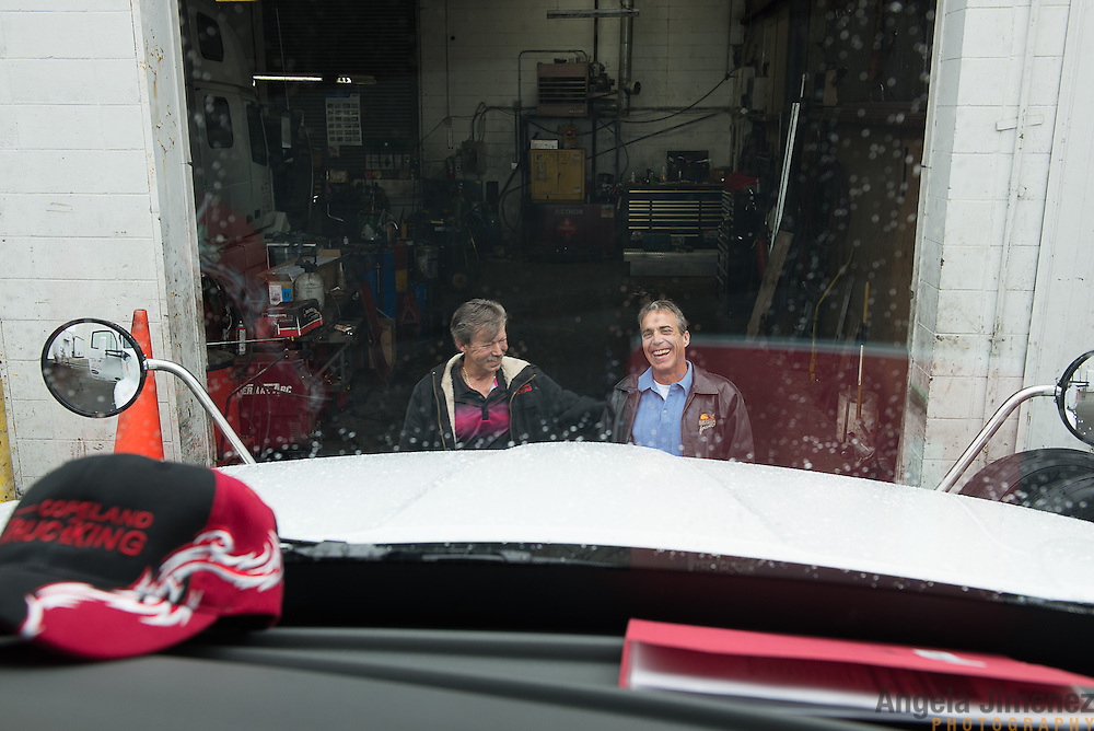 Truck driver Driver Bill McMahon, who was recently rehired by his former employer Copeland Trucking (co-owner Tim Hoag, McMahon's boss is at right) prepares to depart soon in a brand new $145,000 rig from the company's location in Fridley, Minnesota on October 2, 2014. The photo is shot from inside the cab of the truck. <br /> <br /> [ Angela Jimenez/Special to the Star-Tribune  angelajime@gmail.com Assignment #20036493A_ SLUG: TRUCK100514_ EXTRA INFORMATION: Minnesota's severe trucker shortage is forcing wages up and creating accommodating working conditions for drivers. That means shorter trips and less time away from family. In Bill McMahon's case, he and Copeland co-owner Tim Hoag struck a deal: McMahon will get to haul a load to his home in California at least once a month, an exception the company made due to the driver shortage.