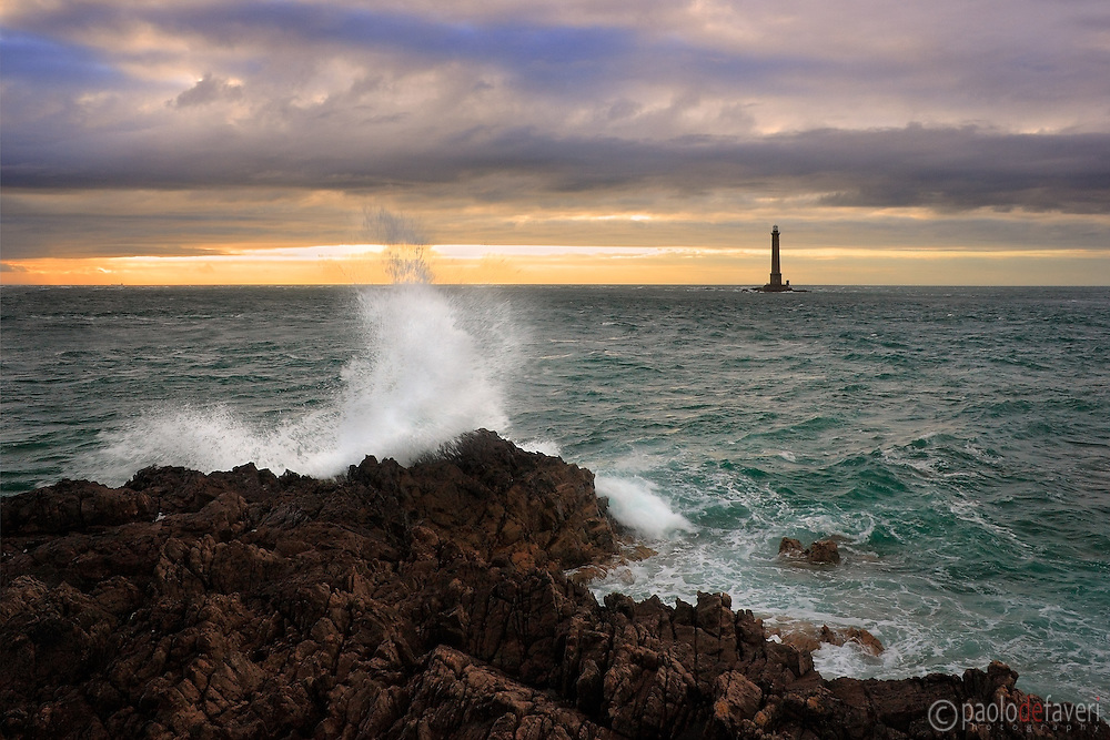 The rugged shoreline of the Cotentin Peninsula near to Goury in Lower Normandy, France. A wave crashing on the reefs at sunset, with the Goury Lighthouse in the background.