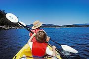 Mother and 5-year old son sea kayaking out of Deer Harbor, Orcas Island, San Juan Islands, Washington.