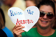 SHOT 7/22/12 6:29:25 PM - Michelle Nelson, 30, of Aurora, Colo. holds up a sign as shooting victims, their families and community members gathered to remember those lost in the movie theater shootings during a prayer vigil at the Aurora Municipal Center in Aurora, Colo. on Sunday evening July 22, 2012. James Eagan Holmes will face charges in the shootings that occurred on Friday July 20, 2012 in which twelve people were killed and another 58 were injured. (Photo by Marc Piscotty / © 2012)